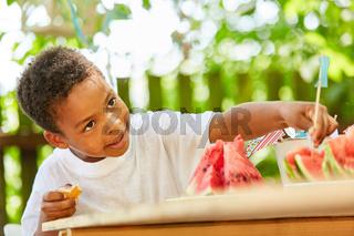 Afrikanischer Junge nascht eine Wassermelone
