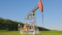 Operating oil and gas well in oil field, profiled against the blue sky
