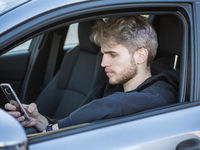 Young Man using mobile phone while driving