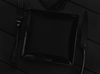 Black empty plate and cutlery on a black table