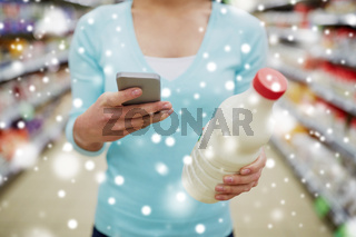 customer with smartphone and milk at supermarket