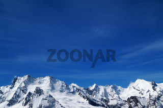 Winter snowy mountains and blue sky in cold sunny day