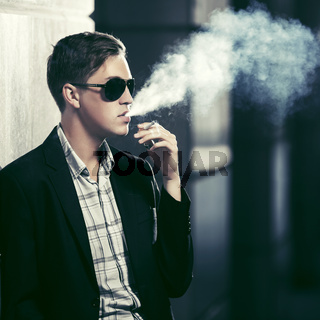 Young fashion man in sunglasses smoking a cigarette in night city street