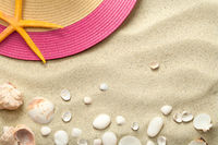 Sand Background with Shells and Summer Hat