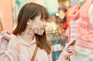 Junge Frau mit Kreditkarte vor Modeladen
