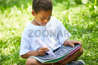 Afrikanischer Junge malt ein Kreide Bild im Garten