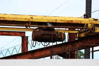 old rusty crane beam in the warehouse under the open sky near the building supermarket for handling operations.
