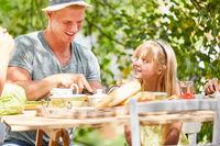 Vater und Tochter beim Frühstück im Garten