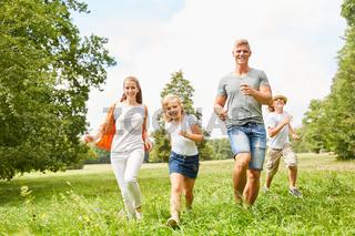 Glückliche Familie und Kinder laufen zusammen