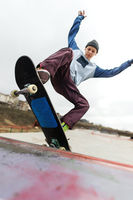 A teenager skateboarder in a hat does a Rocks trick on a ramp in a skate park against a cloudy sky and sleeping area. The concept of urban style in sport