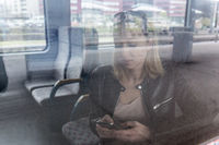 Young woman traveling by train, using smart phone.
