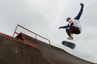 Teenager skateboarder in a cap doing a trick jump on a half pipe on a cloudy sky background