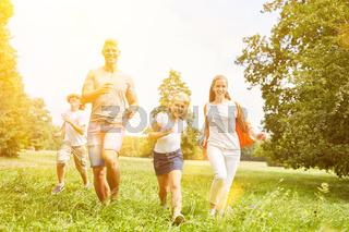 Glückliche Familie und Kinder laufen zusammen als Sport