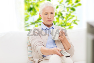 senior woman watching tv and drinking tea at home