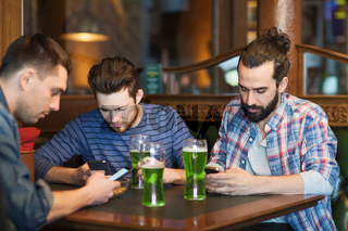 friends with smartphones and green beer at pub