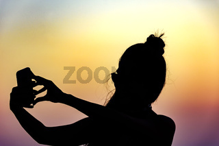Silhouette of girl with smartphone