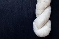 weißes ungefärbtes Wollknäuel auf schwarzer Schieferplatte