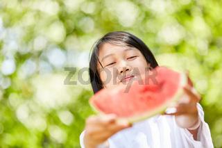Asiatisches Mädchen verteilt ein Stück Wassermelone