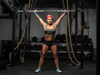 Full length portrait of muscular woman in a gym doing heavy weight exercises