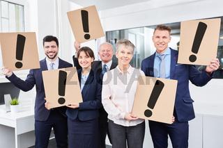 Business Leute halten Ausrufezeichen im Büro