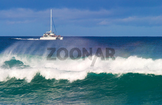 A catamaran off the coast of Kauai with a big wave in the foreground