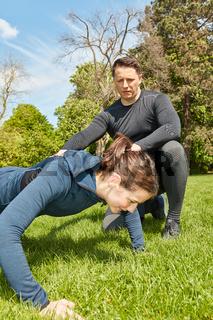 Frau macht Liegestütz bei Personal Trainer