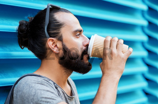 man drinking coffee from paper cup over wall