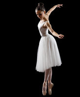Young ballerina isolated on black
