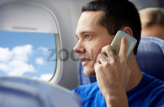 young man calling on smartphone in plane
