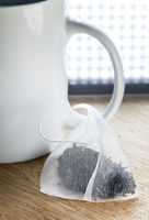 Single bag of elite tea in silk fabric packing and tea mug on a wooden background