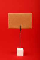 Blank brown kraft paper sign over red background
