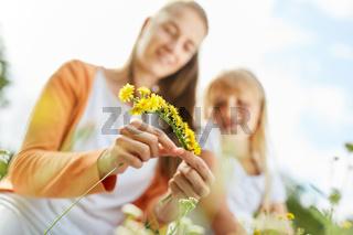 Frau bindet aus Blüten einen Blumenkranz
