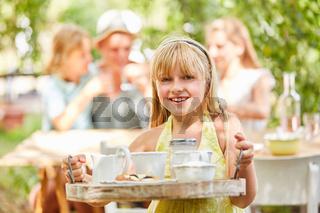 Mädchen tragt Geschirr auf einem Tablett