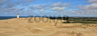 Lighthouse slowly disappearing under a big sand dune. Blue sea and summer clouds. Rubjerg Knude.