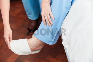 Hände helfen beim Hausschuhe anziehen