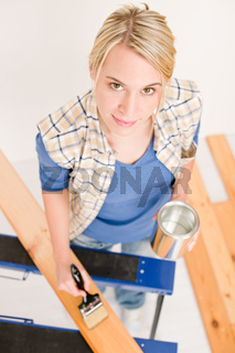 Home improvement - handywoman painting wooden plank