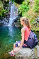 Dutch woman sitting on rock near waterfall