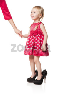 Smiling little girl wearing big shoes kipping hand of her mother