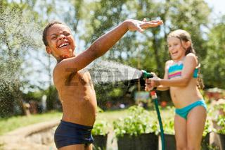 Zwei Kinder bespritzen sich mit Wasser