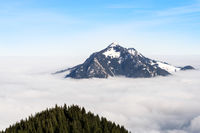 Mountain stick out of foggy cloud layer. Gruenten, Bavaria, Germany. Foresight and vision for business concept and ideas.
