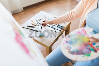 artist washing paintbrush at art studio