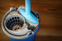 mop and blue bucket ready for cleaning wooden parquet floor