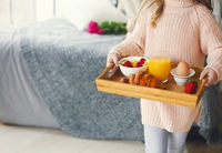 Small girl holding tray with breakfast with tulips on background