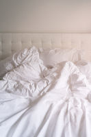Unmade bed with plain white bed linen