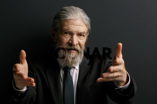 Stylish grey haired man showing hands.