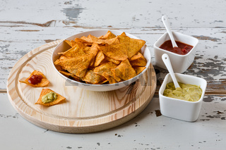 Nachos chips with sauce on a chopping board