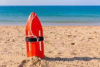 Orange buoy stands in sand on beach