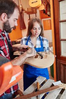 Handwerker und Frau als Lehrling