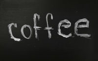 White chalk COFFEE word over black chalkboard