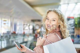 Lächelnde Frau beim Shopping mit Smartphone